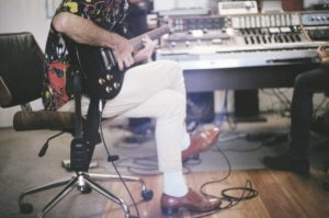 man recording electric guitar in studio